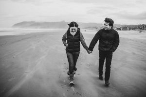 B&W image of a couple walking along the beach on a cold day
